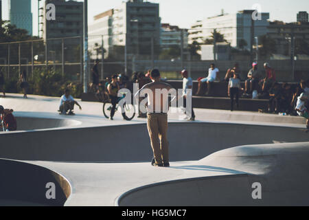 BARCELONA, SPAIN - JUNE 6, 2016: rear view of topless young man in beige trousers with a lot of tattoos watching - Stock Image