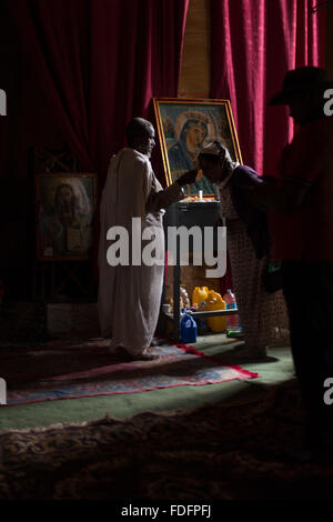 Red curtains catch the low light inside a stone-cut church near Mekele in Ethiopia - Stock Image