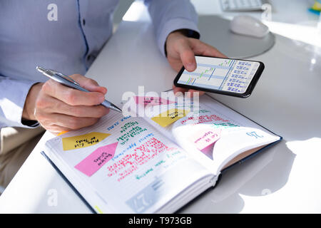 Close-up Of Person Hands With Mobile Phone And List Of Work In Diary - Stock Image