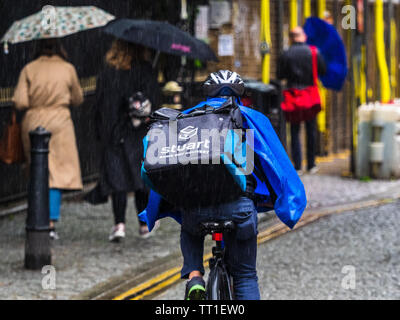 A Stuart company food delivery courier rides through London rain. Stuart is competing with Deliveroo and Uber Eats in this competitive market - Stock Image