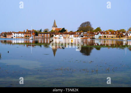 Old village houses and church reflected in still waters of Bosham Creek at high tide in Chichester harbour. Bosham, West Sussex, England, UK, Britain - Stock Image
