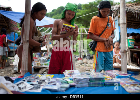 A Hanunoo Mangyans browse DVD titles for sale at a Mangyan market near Mansalay, Oriental Mindoro, Philippines. - Stock Image