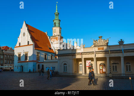 View of people walking through Poznan Old Town Square with the Town Hall (left) and Wielkopolska Military Museum (right), Poznan, Poland. - Stock Image