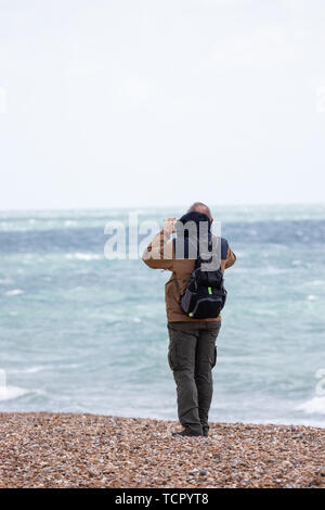 A man using his mobile phone or cell phone to take a photo at the seaside - Stock Image