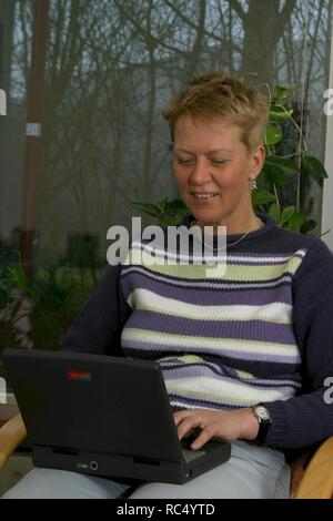 Over 40 European woman using laptop in the 2000s, at home, on lap. - Stock Image