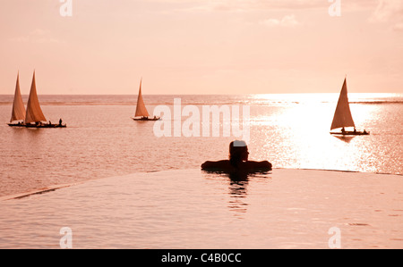 Zanzibar, Matemwe Bungalows. A tourist stands at the edge of an infinity pool watching the Dhows. MR. - Stock Image
