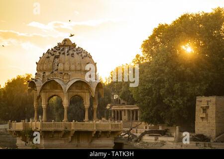 Spectacular view of the Gadi Sagar Lake (Gadisar) with an ancient temple during sunset. - Stock Image