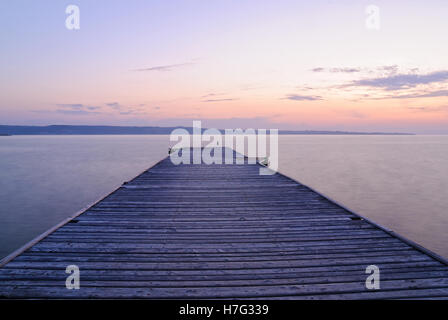 old wooden jetty on the lake at sunset - Stock Image