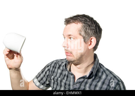 Picture of a man in panick because of an emtpy coffee cup - Stock Image