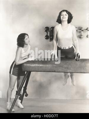 Gymnasts taking turns on pommel horse - Stock Image