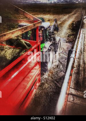 Tractor driving through a river. - Stock Image
