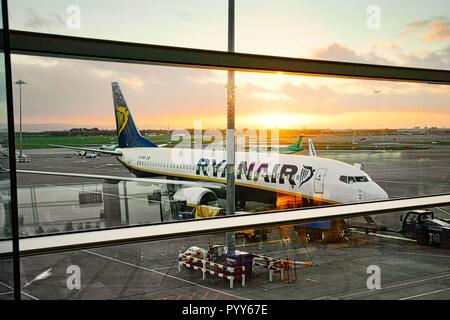 Ryanair passenger plane jet aircraft airplane on runway apron between flights seen from boarding gates of Dublin Airport Terminal Building, Ireland - Stock Image