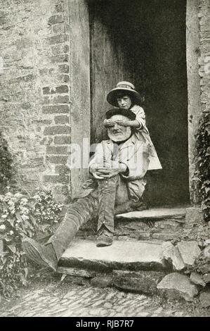 Grandfather and granddaughter in a cottage doorway, England -- the girl is covering his eyes as part of a game. - Stock Image