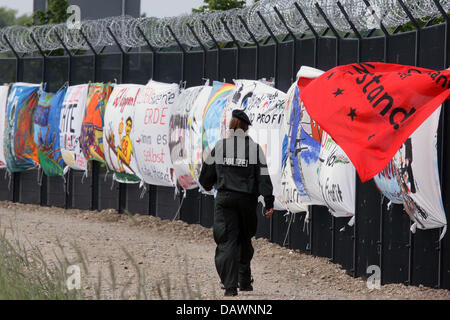An policewoman walks past banners at the security fence in Heiligendamm, Germany, 01 June 2007. The banners form - Stock Image