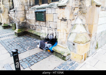 Vagrant homeless person man on streets of York city UK England - Stock Image