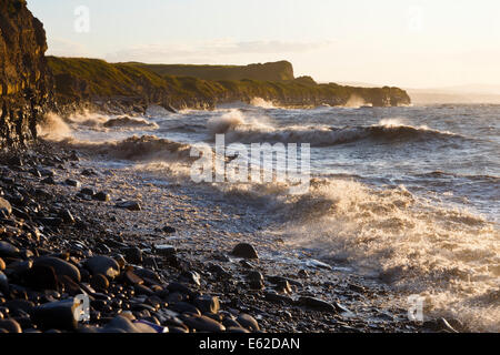 High tide at Kilve beach. Waves eroding more of the cliff face. - Stock Image