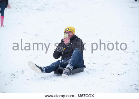 Nottingham, England, 1 March 2018 Young man taking a selfie video sledging in front of Wollaton Hall in snow from - Stock Image