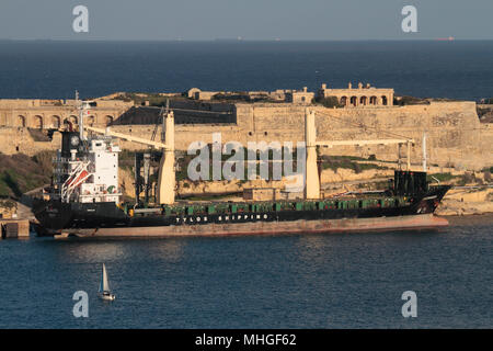 The Tylos Shipping container ship Avonmoor moored next to Fort Ricasoli in Malta's Grand Harbour - Stock Image