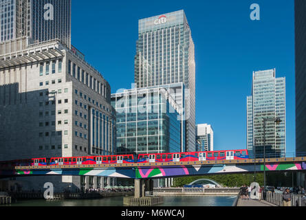 A Docklands Light Railway train passes by modern skyscrapers in Canary Wharf, Londons financial district, London, - Stock Image