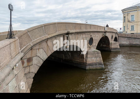 Lone pedestrian crossing stone arch bridge over Fontanka River at Summer Garden that connects Palace & Kutuzov Embankments, St Petersburg, Russia - Stock Image