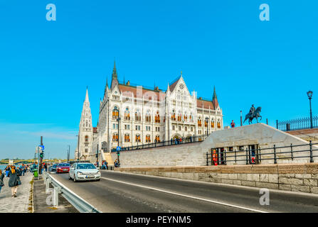Tourists and cars travel the waterfront avenue along the river Danube with the Hungarian Parliament building in view in Budapest, Hungary - Stock Image