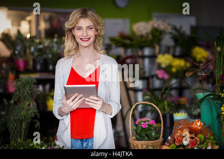 Happy female florist holding digital tablet in flower shop - Stock Image