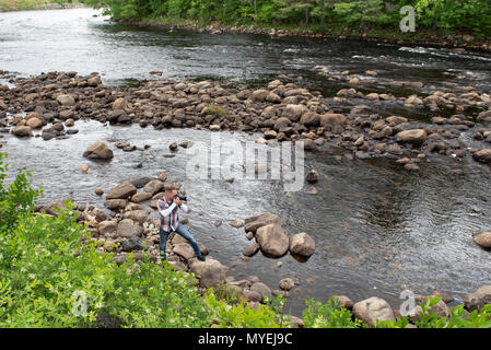 A photographer standing on the rocks on the edge of the Hudson River near North River, NY USA in the Adirondack Mountains - Stock Image