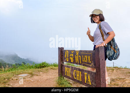 Tourist teen girl hiker wear cap and glasses with backpack smiling thumb up near nameplate attractions of Phu Chi - Stock Image