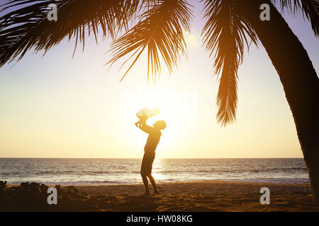 Happy father daughter fun sunset palms - Stock Image