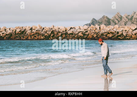 Man traveler enjoying ocean view on empty beach traveling in Norway active vacations outdoor journey lifestyle - Stock Image