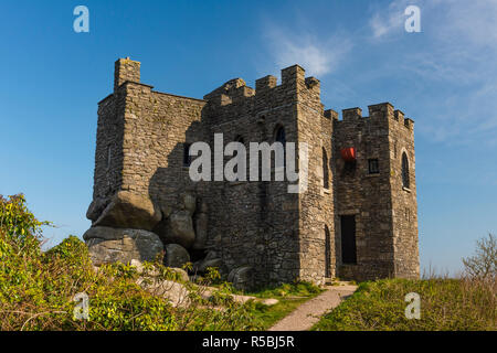 Carn Brea Castle stands on a hill overlooking Redruth, Cornwall, England. The castle was built in the 14th century as a chapel, and was rebuilt in the - Stock Image