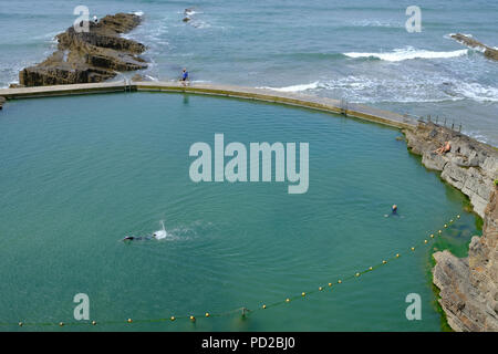 Bude, Cornwall, UK. Swimmers enjoy the hot weather and the water in one of Bude's semi-natural sea bathing pools - Stock Image