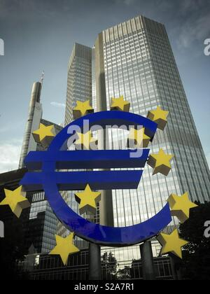 Euro sign statue in front of skyscrapers in Frankfurt am Main, Germany, Europe - Stock Image