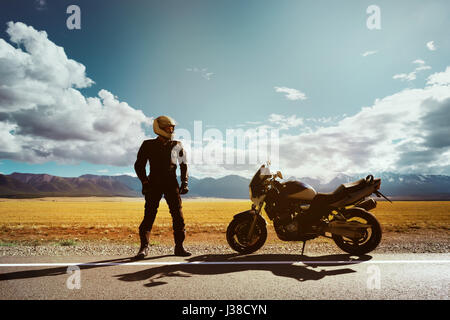 Biker with motorcycle stands on the road on background of mountains. Space for text - Stock Image