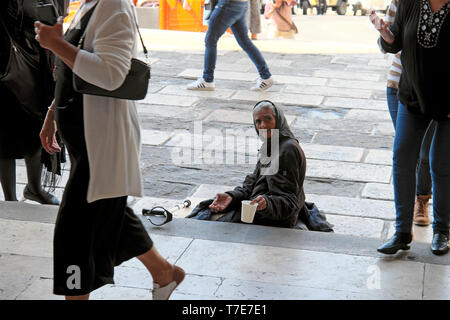 Poor woman sitting on the steps of a church holding out a cup and begging for money while people walk past in Lisbon Portugal Europe EU  KATHY DEWITT - Stock Image