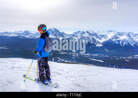 Young skier standing at the edge of a mountain range in Lake Louise at the Canadian Rockies of Alberta, Canada. - Stock Image