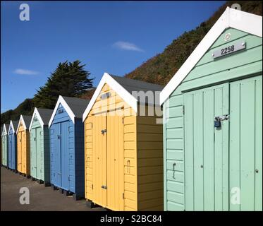 A row of colourful beach huts basking in the summer sunshine. Photo Credit - © COLIN HOSKINS. - Stock Image