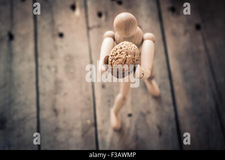 Wooden figure holding walnuts on an old wooden table. - Stock Image