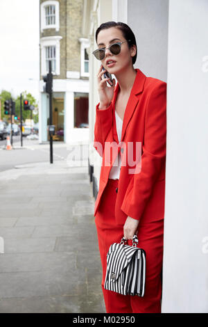 Chic woman in red suit using phone in the street - Stock Image