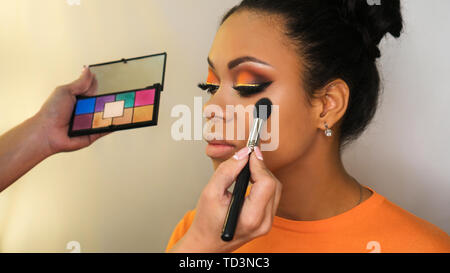 Makeup artist working with African American model in beauty salon face sculpt. Contouring. Contour and highlight makeup. Perfect skin facial. - Stock Image