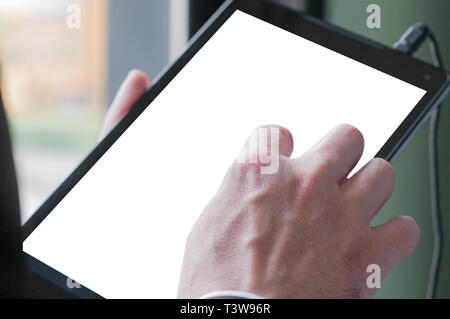 Business man holding a blank screen tablet in the office - Stock Image
