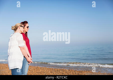 Affectionate lesbian couple holding hands on sunny ocean beach - Stock Image