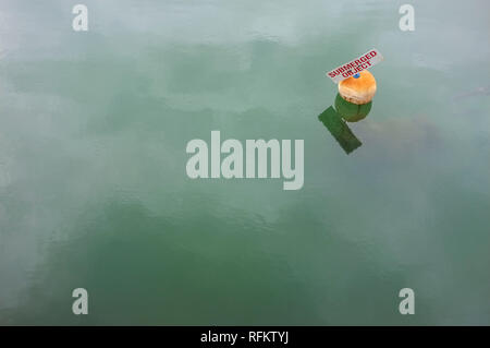 A buoy with the words Submerged Object, written on it to warn boats of a danger. - Stock Image