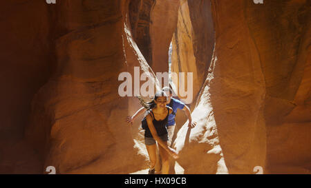 High angle view of boyfriend and girlfriend exploring cave in scenic rock formations - Stock Image
