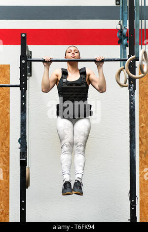 Young woman athlete doing weighted pull-ups on a bar wearing a heavy jacket to strengthen her upper body muscles in a health and fitness concept - Stock Image