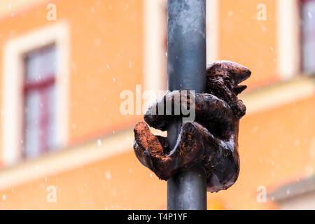 One of the brass gnomes (krasnale, krasnoludki) hanging onto a street light in Wrocław, Wroklaw, Poland - Stock Image