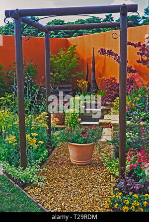 A colourful urban show garden with planted containers of flowers and a seating area - Stock Image
