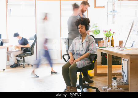 Serene woman meditating with headphones in office - Stock Image