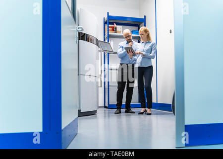 Businessman and businesswoman looking at tablet at 3d printer - Stock Image