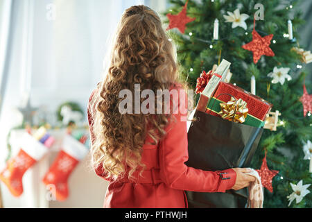 Seen from behind modern woman in red trench coat with shopping bag full of Christmas present boxes near Christmas tree - Stock Image